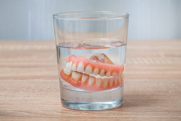 Full, Dirty Dentures In A Glass Of Water For Cleaning