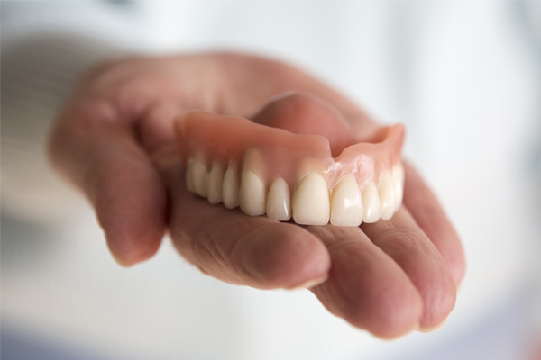photo of top dentures sitting in palm of hand at Denture Clinic in Liverpool