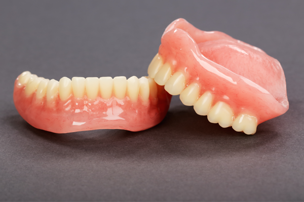 complete dentures on grey background at Denture Clinic in Liverpool