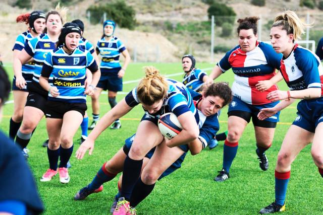 photo of a ladies rugby team wearing mouth guards playing with a tackle at the forefront