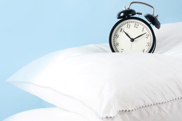 Alarm Clock On Top Of A White Pillow On Blue Background