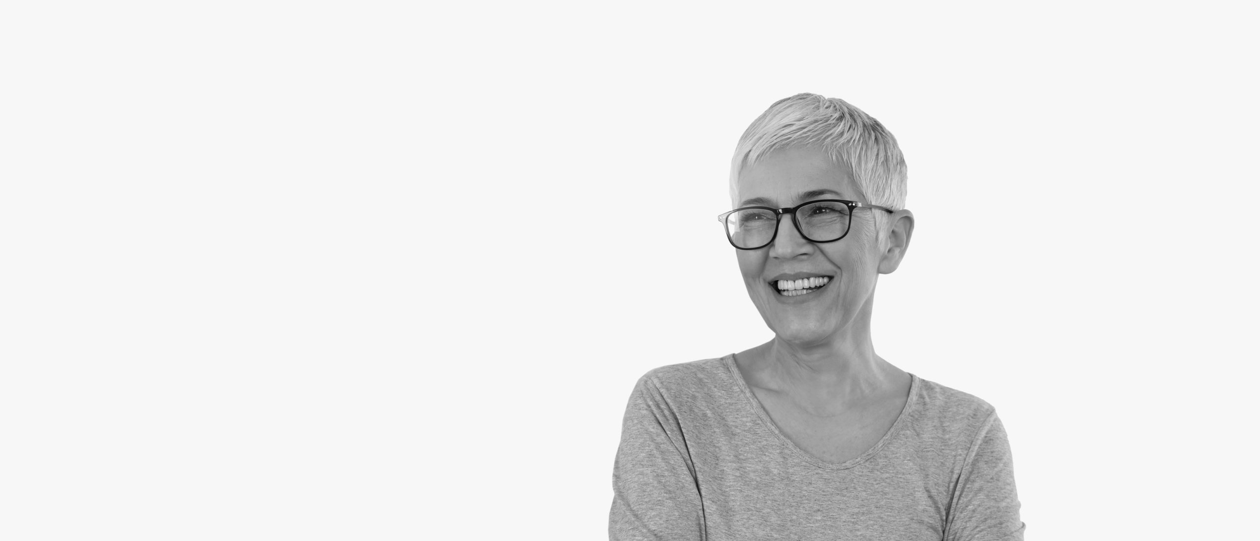 lady with glasses in black and white on light grey background smiling showing full dentures