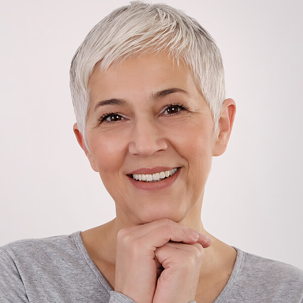 Middle aged lady with grey hair and grey jumper smiling for an e-consultation